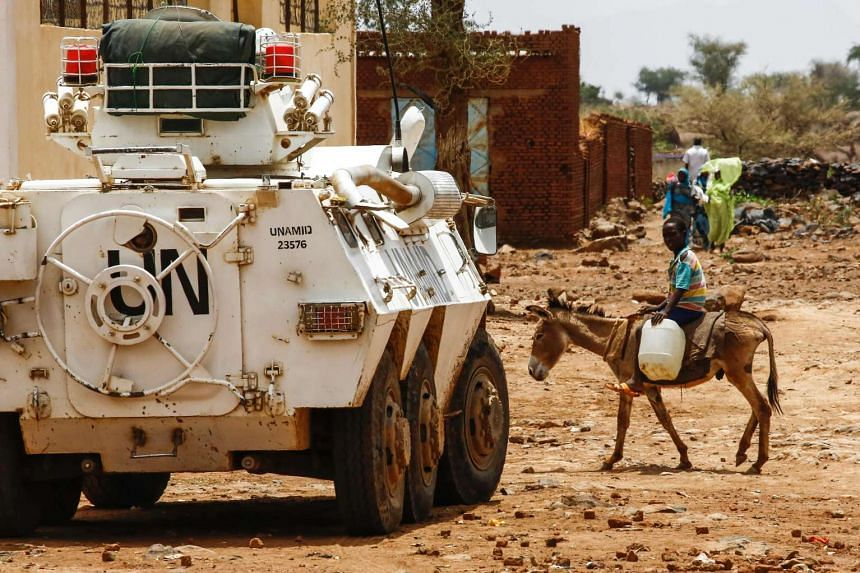 A Sudanese boy rides a donkey past a UNAMID armoured vehicle in the war-torn town of Golo, June 19, 2017.