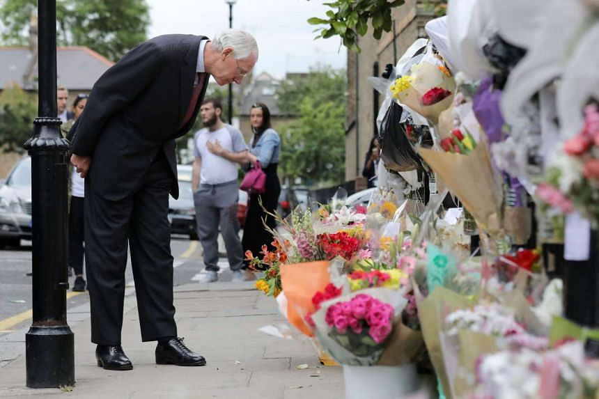 Sir Martin Moore-Bick, who will lead a public inquiry into the fire, looks at flowers left in tribute to the victims.