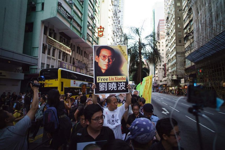 A pro-democracy protester holding up a placard with a picture of Chinese Nobel laureate Liu Xiaobo on it during a demonstration in Hong Kong on June 30, 2017.