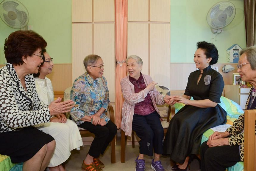Wife of China's President Xi Jinping, Peng Liyuan (second from right), chatting with residents during her visit to an elderly care facility in Hong Kong on June 30, 2017.