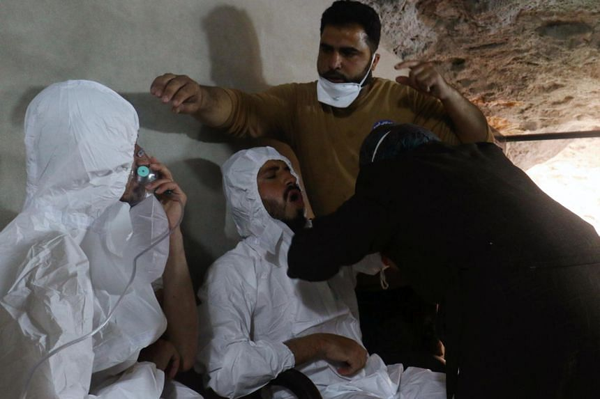 A man breathing through an oxygen mask as another one receives treatments, after what rescue workers described as a suspected gas attack in the town of Khan Sheikhoun in rebel-held Idlib, Syria on April 4, 2017.