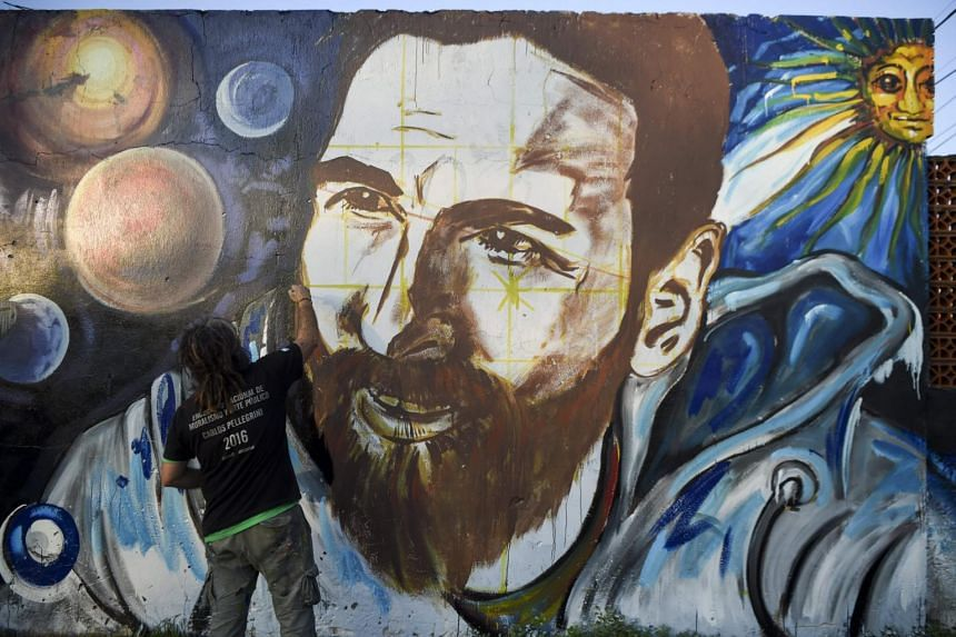 Artist Lisandro Urteaga painting a mural of Barcelona's football star Lionel Messi at the footballer's birthplace in Rosario, Santa Fe province, Argentina on June 29, 2017.