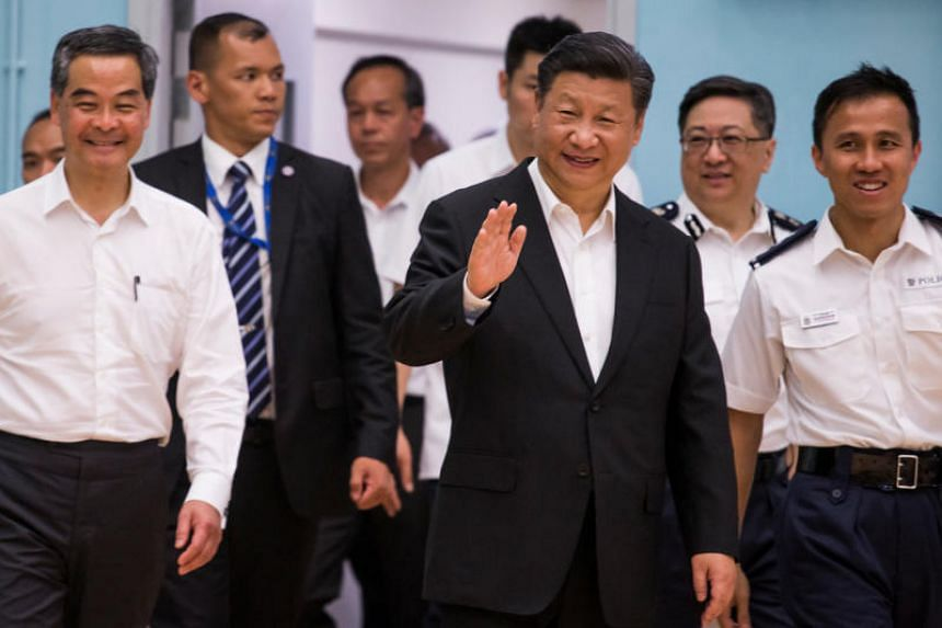 Chinese President Xi Jinping waves as he arrives with Leung Chun-ying during a visit at the Hong Kong Police Force's Junior Police Scheme Permanent Activity Center and Integrated Youth Camp in Hong Kong, China, on June 30, 2017.