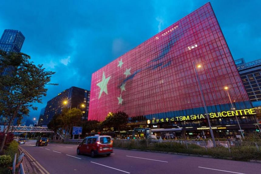 Traffic drives by a giant electronic billboard showing a Chinese flag on the side of a building in Tsim Sha Tsui, Hong Kong, China, on June 24, 2017.