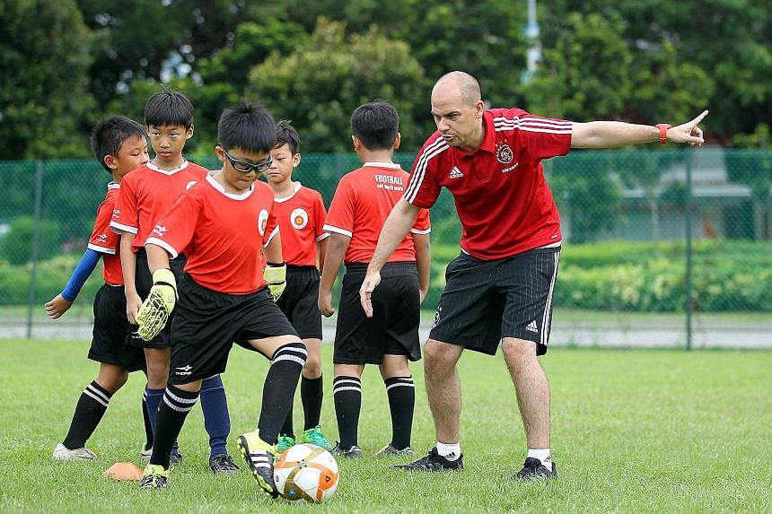 Ajax youth coach Casimir Westerveld with children from ActiveSG Football Academy. The writer says the lack of youngsters participating in competitive football beyond the youth level is an issue.