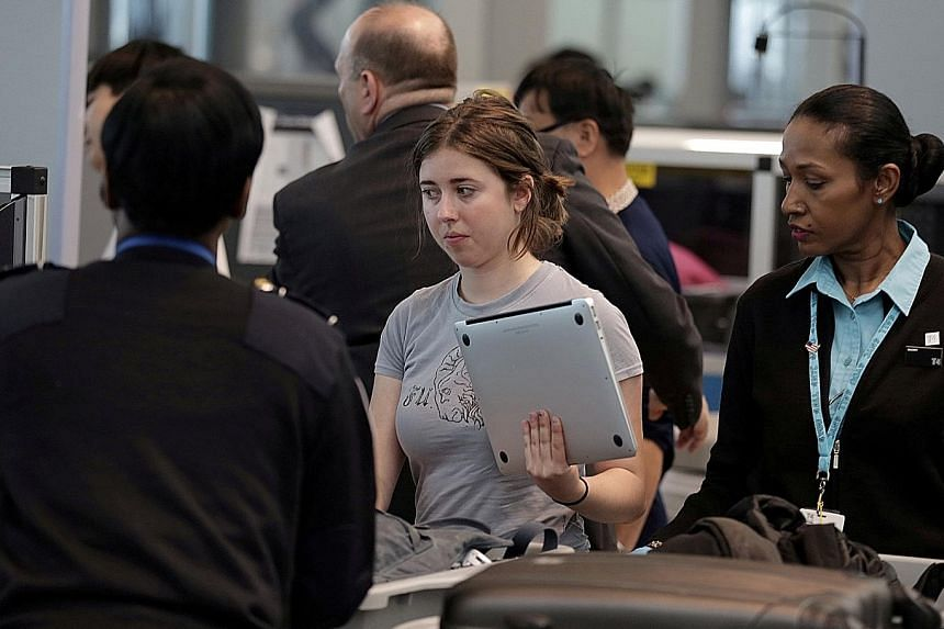 A traveller waiting for her laptop to be scanned at the John F. Kennedy airport in New York City.