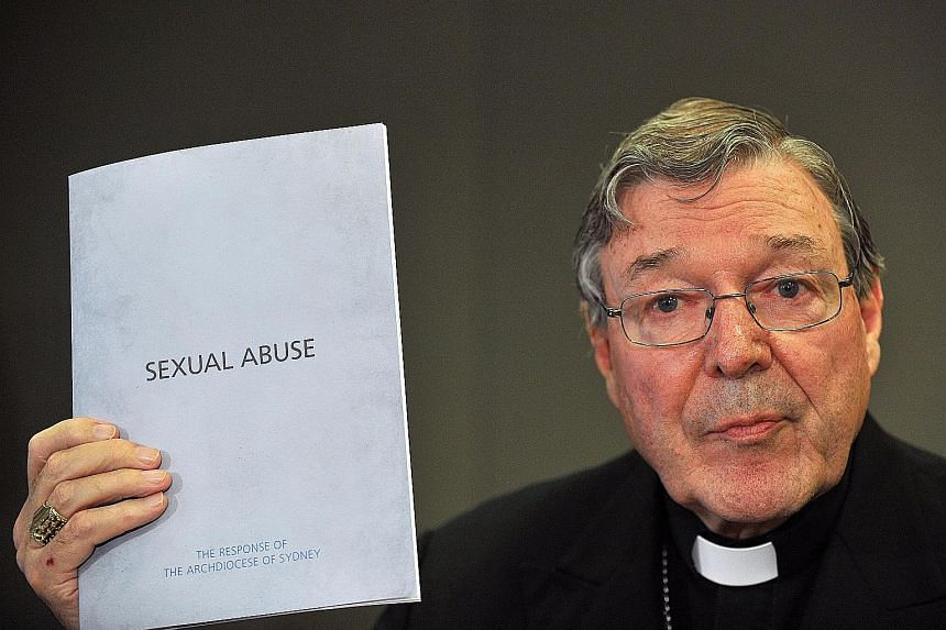 Cardinal George Pell with a folder outlining the Catholic Church's response to Australia's inquiry into sexual abuse in November 2012. Pell now faces multiple charges relating to historical sex offences.