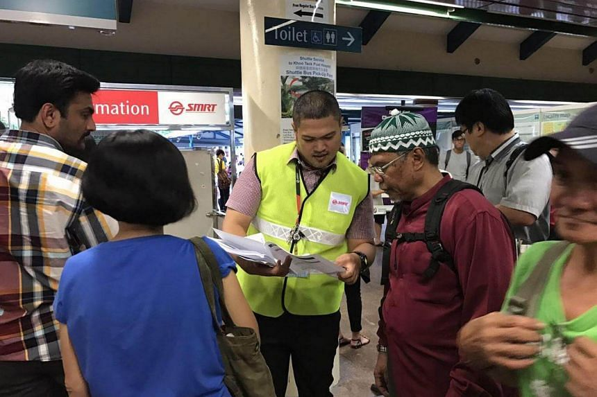 An SMRT employee in Yishun handing out pamphlets on alternative modes of transport to commuters, on June 2, 2017, during the North-South Line delay.
