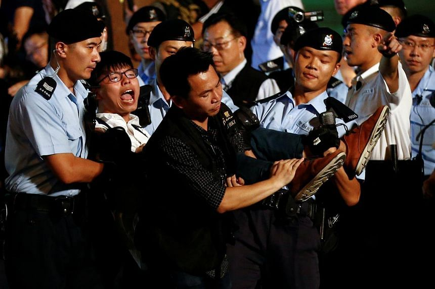 Student protest leader Joshua Wong shouting as he is carried by policemen, on June 28, 2017.