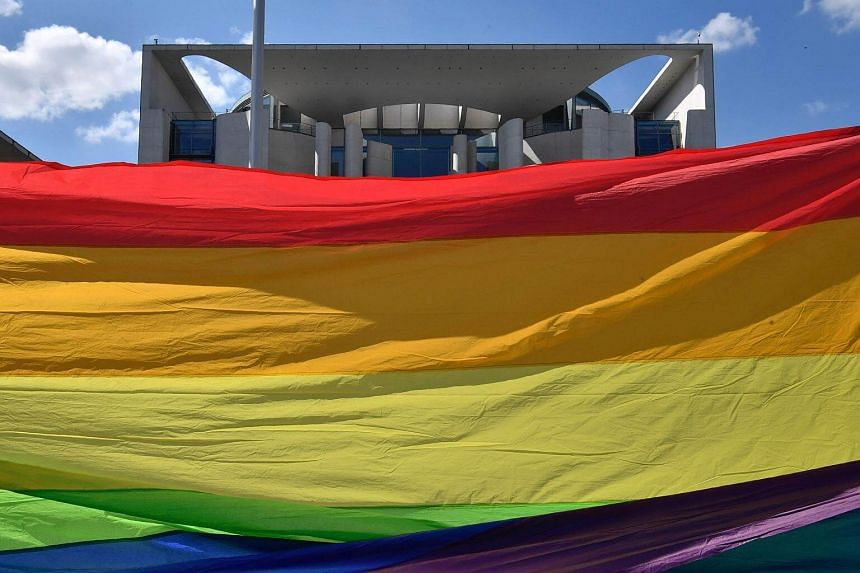 Activists stretch a giant rainbow banner in front of the Chancellery in Berlin on April 30, 2017.