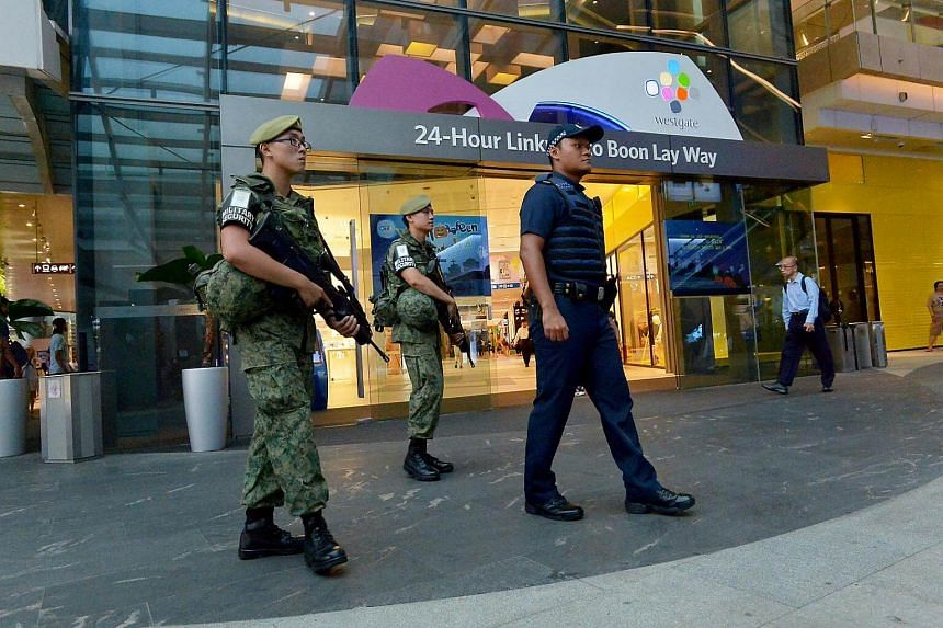 Singapore Police Force (SPF) and Singapore Armed Forces (SAF) personnel patrolling at Westgate shopping centre.