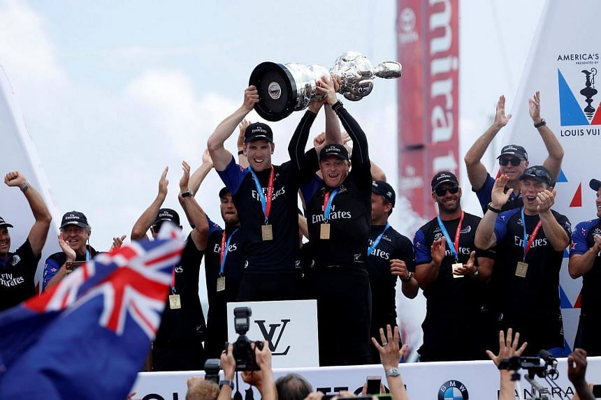 Peter Burling, Emirates Team New Zealand Helmsman celebrates with Skipper Glenn Ashby as they hold the America's Cup trophy after defeating Oracle Team USA.