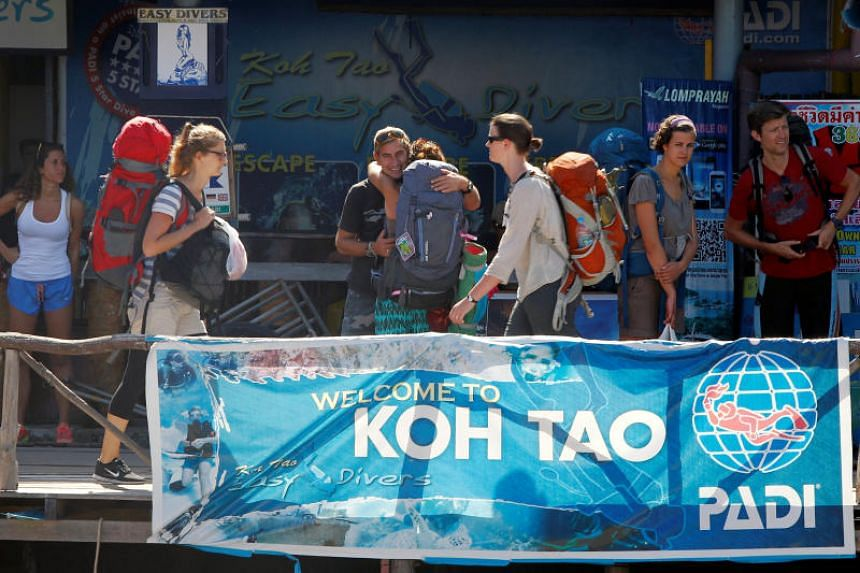 Tourists carry their backpacks after arriving by boat to the island of Koh Tao, Surat Thani province, Thailand.