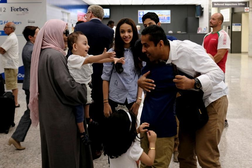 A Saudi family embraces each other as members arrive at Washington Dulles International Airport after the US Supreme Court granted parts of the Trump administration's emergency request to put its travel ban into effect.