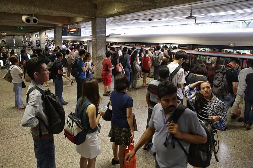 Commuters queuing up to board a train at Ang Mo Kio MRT station.
