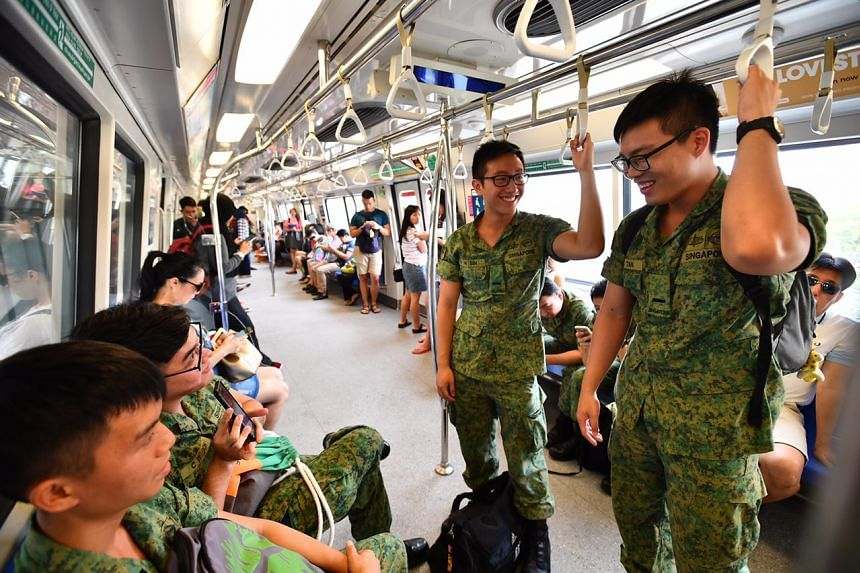 NSF 2LT Justin Sim, (standing left) 20, and NSF 2LT Tan Ting Jun, (standing right) 20, both platoon commanders at BMTC, on the train from Pasir Ris MRT station.