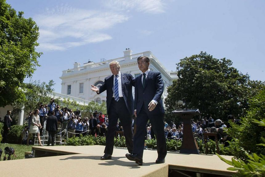 Trump (left) and Moon turn away from the podiums after making joint statements in the Rose Garden.