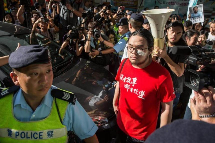 Democracy activists walk to a police van while surrounded by police, as they are blocked by pro-Chinese activists, in Hong Kong, China, on July 1, 2017.