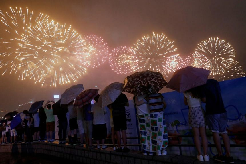 People watching fireworks over Victoria Harbour as part of the celebration for the 20th anniversary of the city's handover from British to Chinese rule, in Hong Kong, China on July 1, 2017.