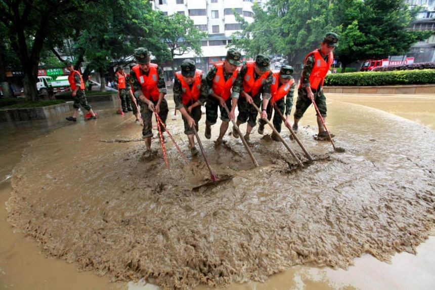 Paramilitary policemen sweep a flooded street in Liuzhou, Guangxi Zhuang Autonomous Region, China, on June 30, 2017