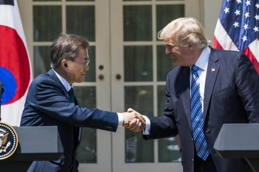 US President Donald Trump (right) and President of South Korea Moon Jae In (left) shake hands as they make joint statements in the Rose Garden of the White House in Washington, DC, on June 30, 2017.