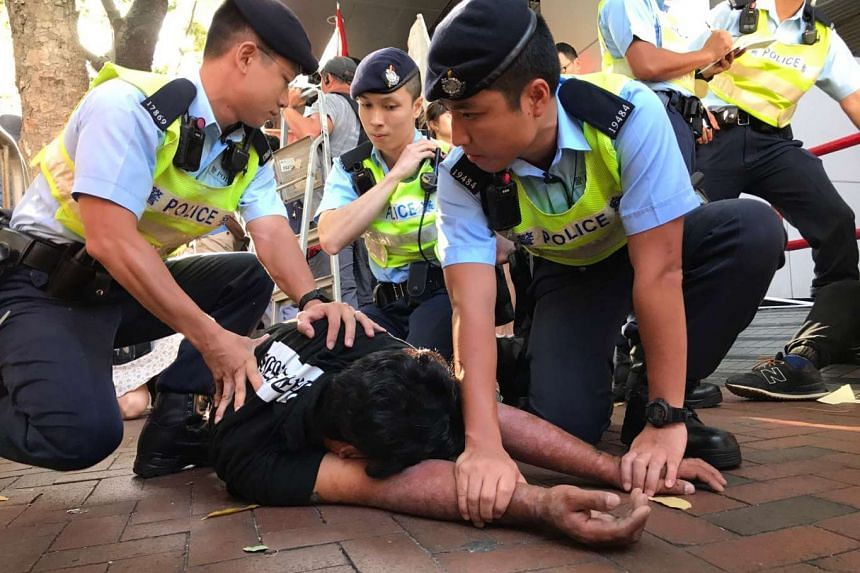 Three policemen were seen pinning down a man believed to have been involved in destroying a prop coffin. Lawmaker Leung Kwok Hung told the media earlier that the coffin was to remind people that the occasion is not worth celebrating.