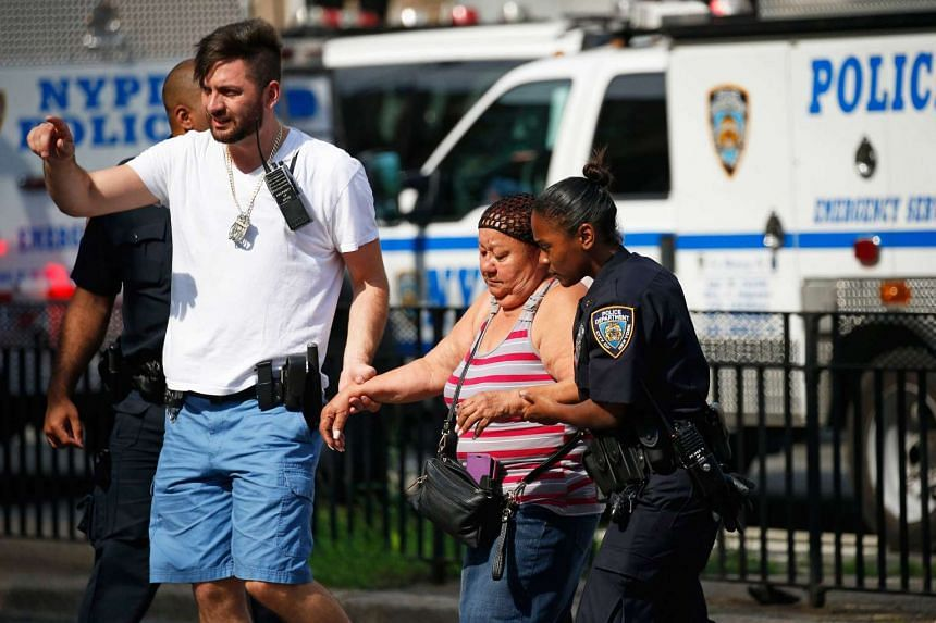 A police officer helps a woman from the scene.