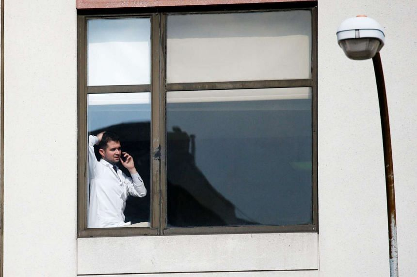 A doctor speaks on the phone inside a hospital where a gunman opened fire, injuring several people in New York City.