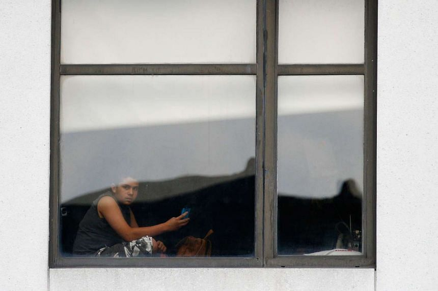 A child looks out the window of the hospital after the shooting.