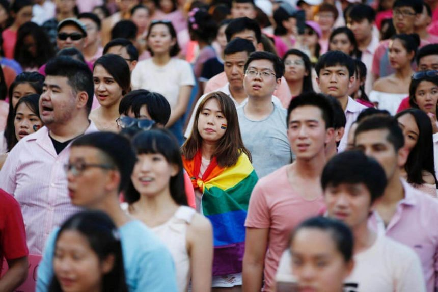 A woman wrapped in the rainbow flag is seen at the Pink Dot rally on July 1, 2017.