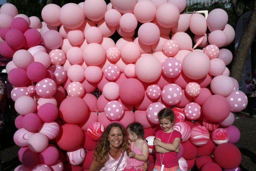 A woman and her two daughters pose for a photograph in front of a pink balloon wall during the Pink Dot event held at the Speaker's Corner in Hong Lim Park, Singapore, on July 1, 2017.