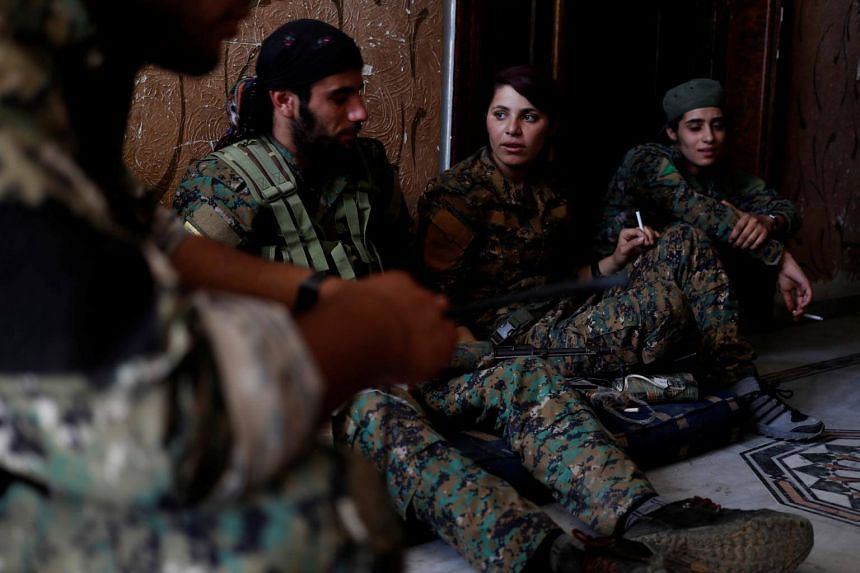 Kurdish fighters from the People's Protection Units (YPG) sit in a house in Raqqa, Syria on June 28, 2017.