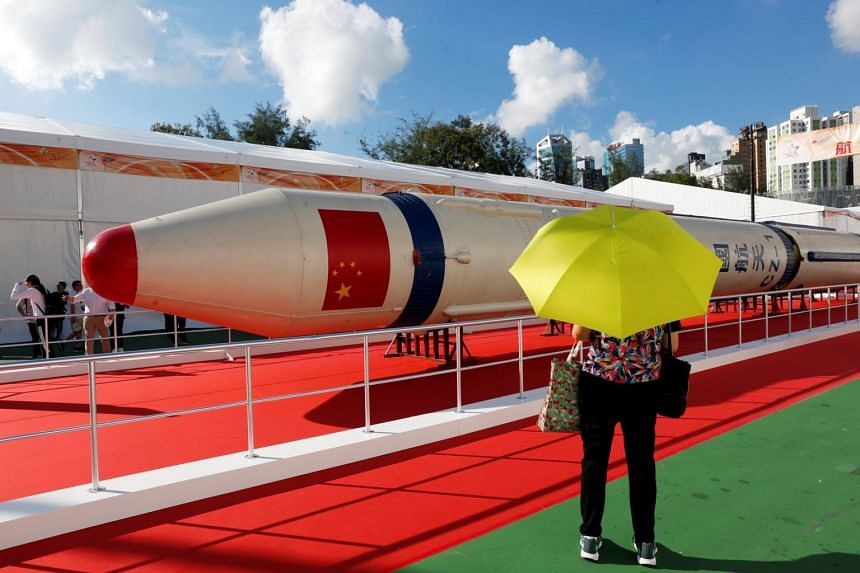 Visitors looking at a Changzheng-1 (CZ-1) or Long March 1 rocket displayed at a high-tech fair, to celebrate the 20th anniversary of the territory's handover to Chinese rule, in Hong Kong, China on June 28, 2017.