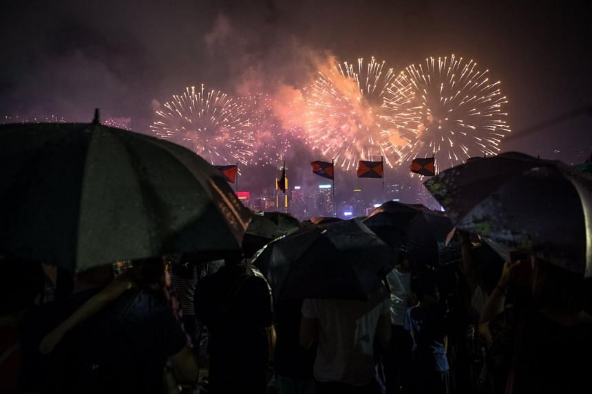 People holding umbrellas under heavy rain at fireworks light up the sky over Victoria Harbour in Hong Kong, China on July 1, 2017.