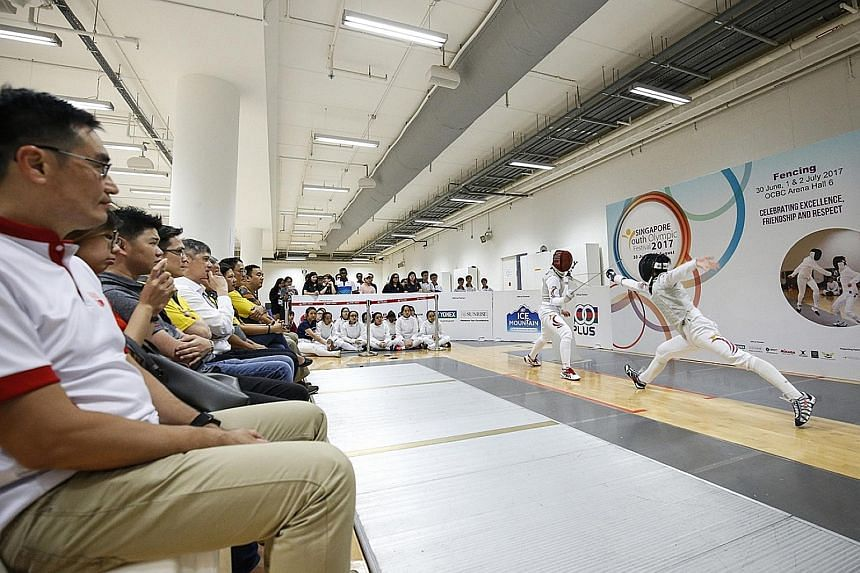 Singapore fencers putting on a demonstration during the opening ceremony of the Singapore Youth Olympic Festival (SYOF) yesterday at the OCBC Arena. The annual multi-sport festival began yesterday and will feature competitions in 12 sports until Aug