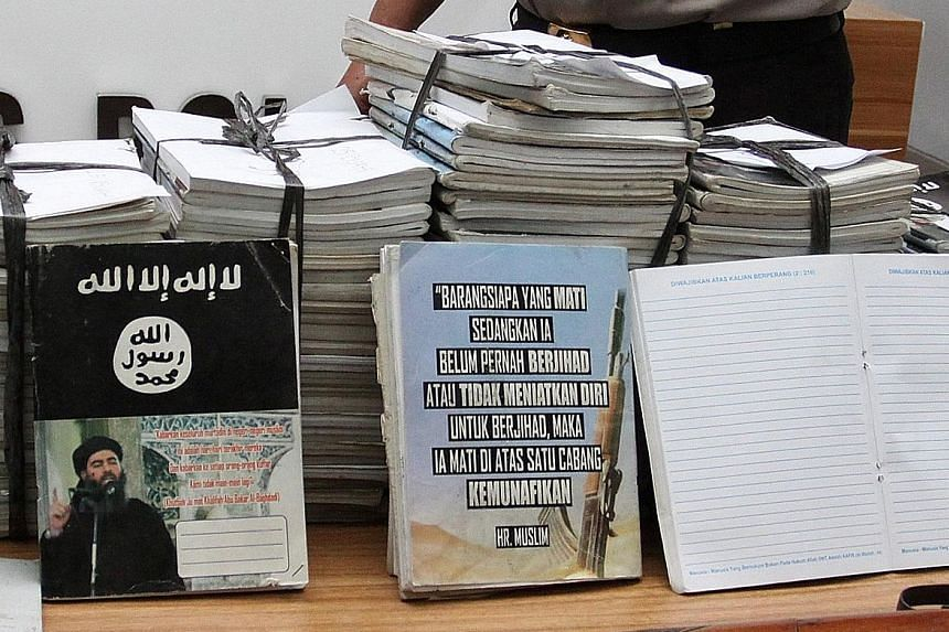 Notebooks inscribed with ISIS propaganda, seized during a raid on the home of a suspected militant, being shown at a press conference in Jakarta yesterday.