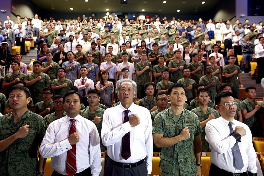 Reciting the SAF pledge at Temasek Polytechnic with NSmen, their employers and civilian colleagues are (from left) Brigadier-General Ong Tze-Ch'in, director of military intelligence; Association of Small and Medium Enterprises (Asme) president Kurt W