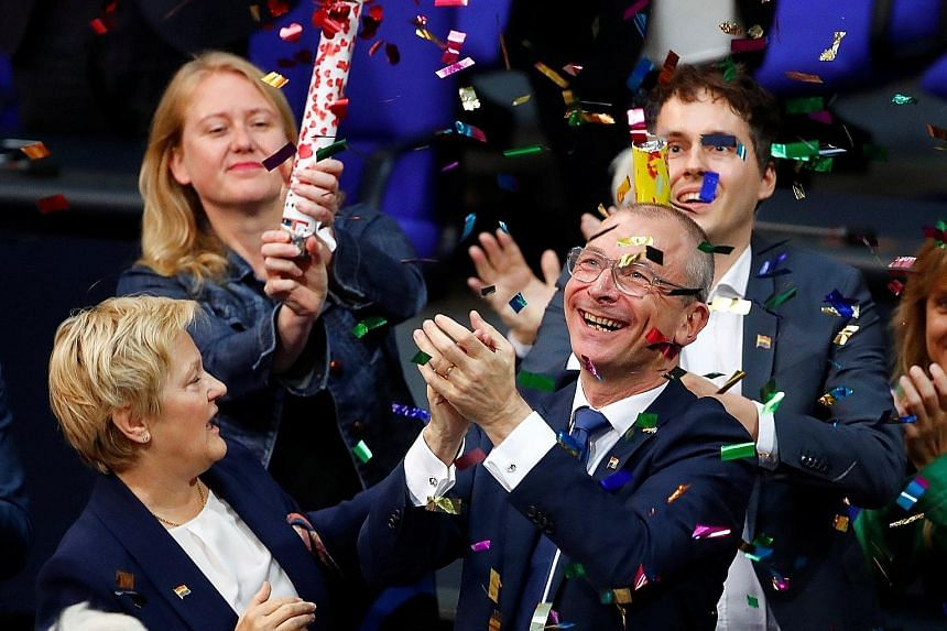 German politician Volker Beck (foreground) celebrating after the gay marriage law was passed in the lower house of Parliament yesterday. The law passed by a margin of 393 to 226, despite the personal objections of Chancellor Angela Merkel.