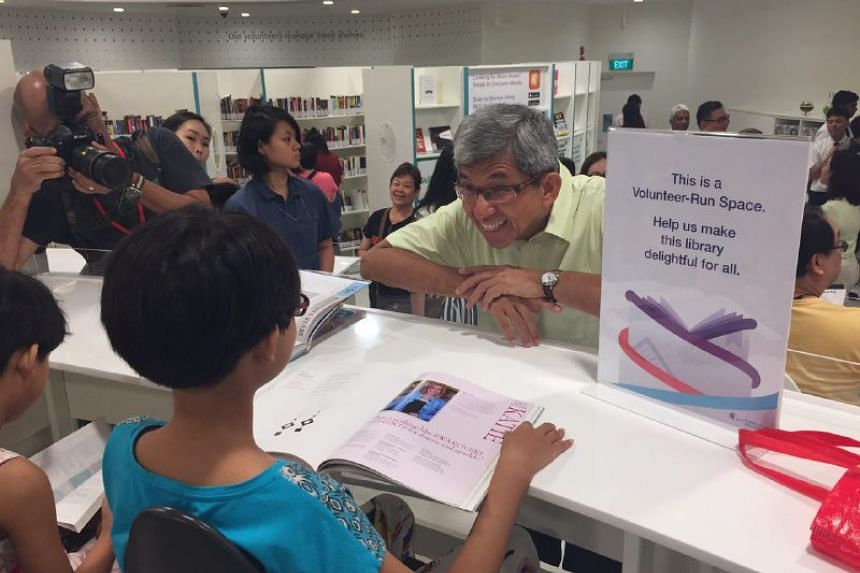 Minister for Communications and Information Yaacob Ibrahim talking to a child at the adult and teens wing of the revamped Bukit Panjang Public Library