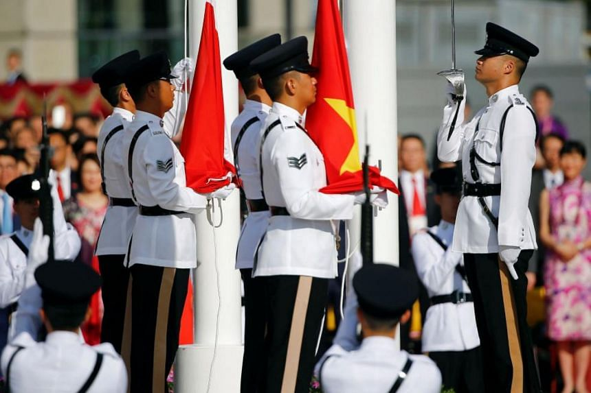 China's and Hong Kong's flags are raised during a ceremony marking the 20th anniversary of the city's handover from British to Chinese rule, in Hong Kong on July 1, 2017.