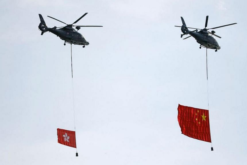 Helicopters carrying China's and Hong Kong's flags over the area where a flag raising ceremony takes place marking the 20th anniversary of the city's handover from British to Chinese rule, in Hong Kong, on July 1, 2017.