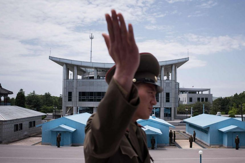 A Korean People's Army soldier gestures as he stands before the military demarcation line separating North and South Korea.