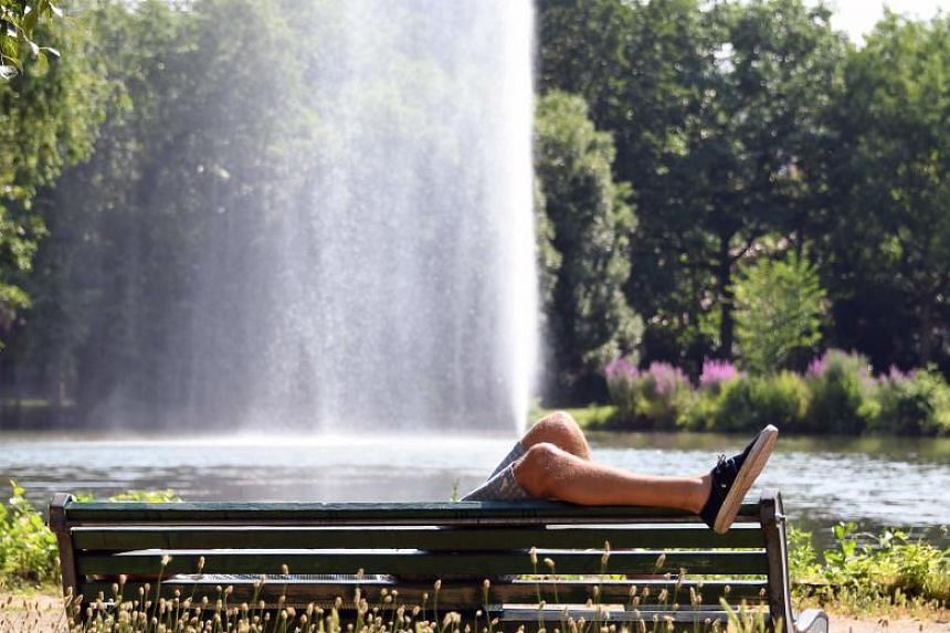 A man lies on a bench on a sunny day in a garden in Toulouse