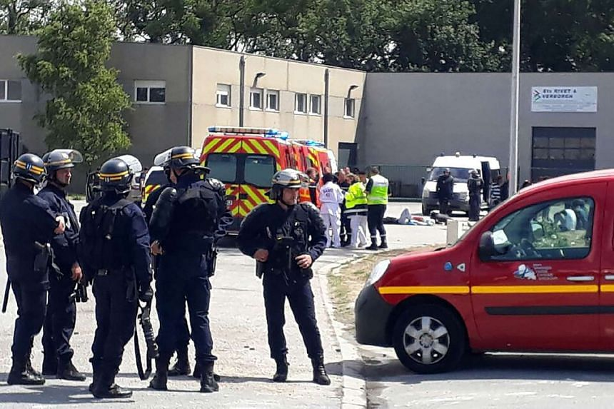 Police officers and emergency workers intervene after clashes between migrants.