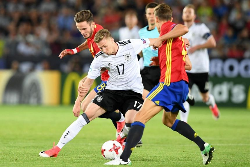 Germany's midfielder Mitchell Weiser (centre) and Spain's midfielder Saul Niguez (left) vie for the ball during the Uefa U-21 European Championship football final match.