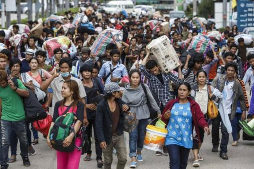 Cambodian migrant workers carry their belongings as they walk to cross the border at Aranyaprathet in Sa Kaew, on June 15, 2014.