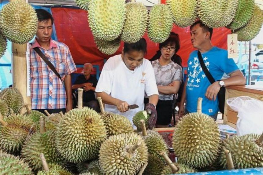 Malaysian durian trader Lim Beng Choo attending to customers at her stall.