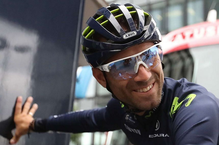 Valverde (above) came down hard on a slippery bend in miserable wet conditions and was visibly in great pain.
