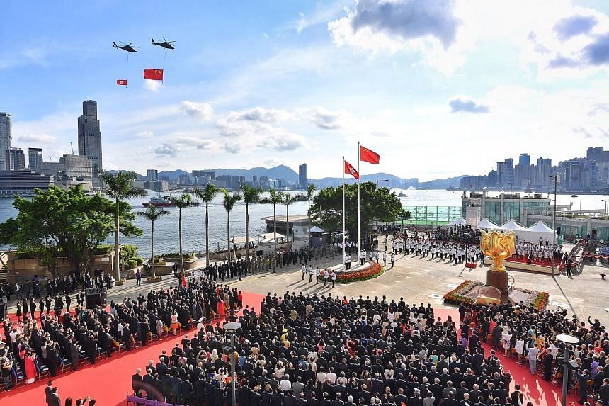 Helicopters carrying the Chinese (right) and Hong Kong flags flying past during a ceremony at Golden Bauhinia Square to celebrate the 20th anniversary of the city's handover to China yesterday. In her speech, new Chief Executive Carrie Lam pledged a