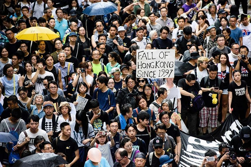 "A protest march in Hong Kong yesterday. Thousands of protesters chanting ""Reclaim Hong Kong"" took to the streets after Mrs Carrie Lam was sworn in as the city's new Chief Executive. More than 20 were arrested."